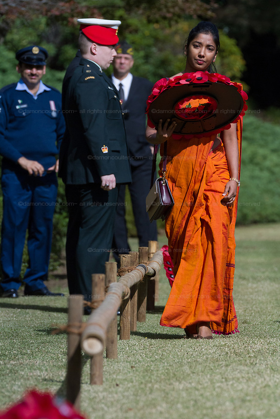 A representative of the Sri Lankan Embassy wears a sari as she lays a wreath of poppies during the Remembrance Sunday ceremony at the Hodogaya, Commonwealth War Graves Cemetery in Hodogaya, Yokohama, Kanagawa, Japan. Sunday November 12th 2017. The Hodagaya Cemetery holds the remains of more than 1500 servicemen and women, from the Commonwealth but also from Holland and the United States, who died as prisoners of war or during the Allied occupation of Japan. Each year officials from the British and Commonwealth embassies, the British Legion and the British Chamber of Commerce honour the dead at a ceremony in this beautiful cemetery.