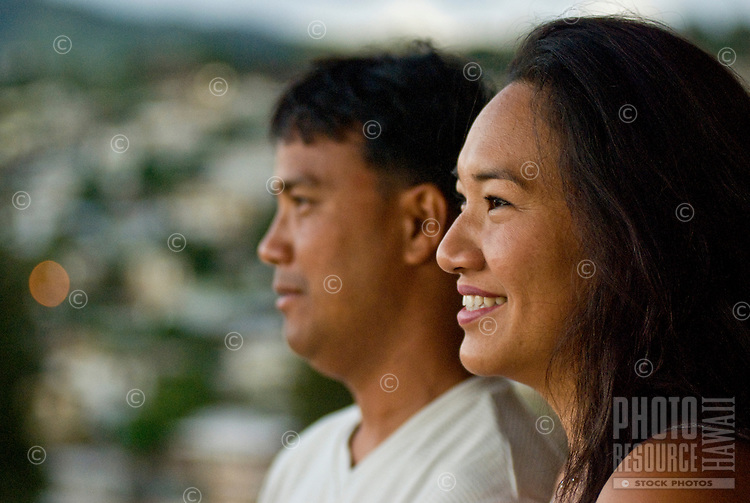 Local part Hawaiian couple at their home in Makakilo with hillside and homes in rear