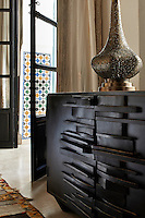 A gold ornament is displayed on a modern, craft style chest of drawers.