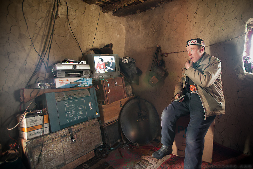 A Kyrgyz man, Haji Bootoo Boi's brother, is watching Kyrgystan channel on one of the few TV with satellite in the Little Pamir - car batteries are powered by solar energy and run the TV set. The equipment was bought in neighboring Pakistan, a week long journey with a yak caravan..The Kyrgyz settlement of Tchelab, near Chaqmaqtin lake, Haji Bootoo Boi's camp...Trekking through the high altitude plateau of the Little Pamir mountains, where the Afghan Kyrgyz community live all year, on the borders of China, Tajikistan and Pakistan.