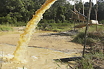 Water being pumped from an unregulated gold mining operation on the Brokopondo reservoir, Suriname.  The man-made lake was hastily created by flooding a vast acreage of jungle without any prior logging and evacuation of animals and is reputed to be polluted by mercury from the mines..
