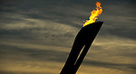 Olympic flame burning silhouetted against a sunset sky during the 2014 Sochi Olympic Winter Games at the Olympic Park on February 8, 2014 in Sochi, Russia. Photo by Victor Fraile / Power Sport Images