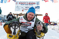 Mats Pettersson hugs his leaders at the finish line in Nome on Thursday March 19, 2015 during Iditarod 2015.  <br /> <br /> (C) Jeff Schultz/SchultzPhoto.com - ALL RIGHTS RESERVED<br />  DUPLICATION  PROHIBITED  WITHOUT  PERMISSION