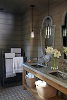 A double marble-topped washstand in the bathroom houses a pair of stainless steel basins complemented with a pair of mirrors on the wood-clad wall
