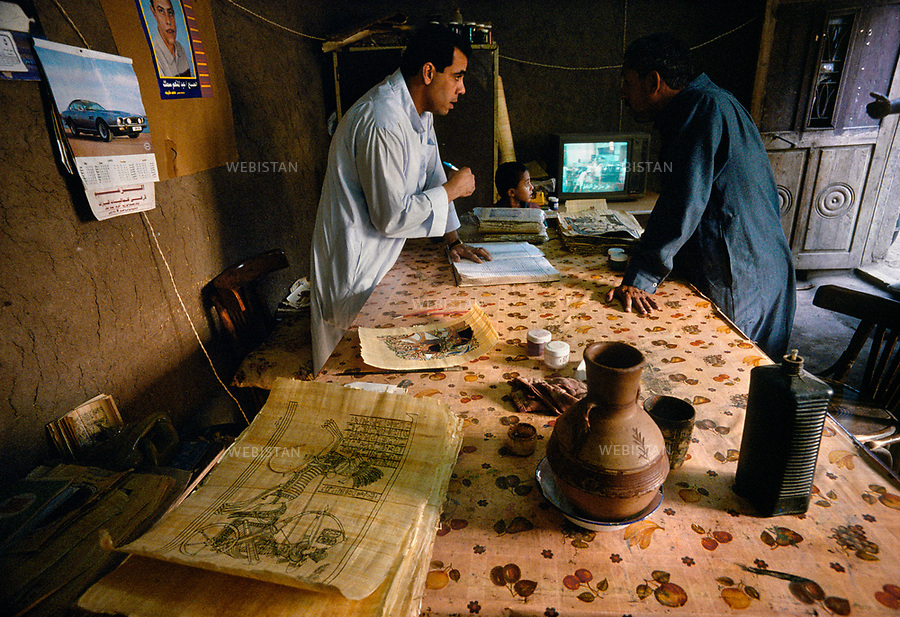 1996. Egypt. Nile delta. El-Qaramus. In a workshop, a craftsman updates a register of the daily fulfilment of the craftmen colorizing the drawings on papyrus. Egypte. Delta du Nil. El-Qaramus. Dans un atelier, un artisan tient à jour un registre des réalisations des artisans qui travaillent à la colorisation des dessins sur papyrus.