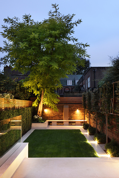 Floor and wall lighting illuminate the paths and brick walls of the garden in the evening