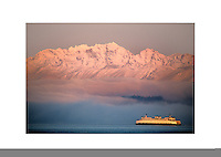 Sunrise highlights a Washington State Ferry as it crosses Puget Sound from Seattle to Bremerton, edging by a fogbank below a snowy Olympic Mountain Range. Washington State.