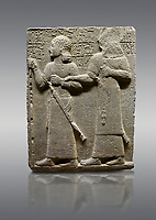 Picture &amp; image of Hittite monumental relief sculpted orthostat stone panel of Royal Buttress. Basalt, Karkamıs, (Kargamıs), Carchemish (Karkemish), 900-700 B.C. Anatolian Civilisations Museum, Ankara, Turkey.<br /> <br /> King Araras holds his son Kamanis from the wrist. King carries a sceptre in his hand and a sword at his waist while the prince leans on a stick and carries a sword on his shoulder. <br /> <br /> Hieroglyphs reads; &quot;This is Kamanis and his siblings. I held his hand and despite the fact that he is a child, I located him on the temple. This is Yariris' image&quot;.  <br /> <br /> Against a gray background.