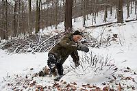 Kinder bauen eine Igel aus Schnee, Stöckchen dienen als Stacheln
