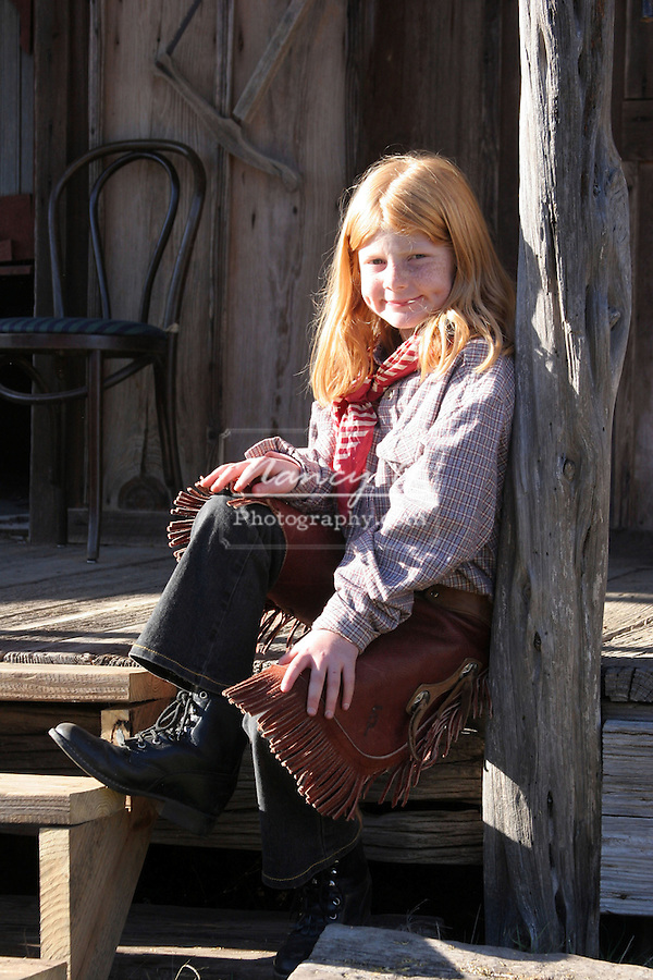 A young cowgirl sitting on the boardwalk in an old west town