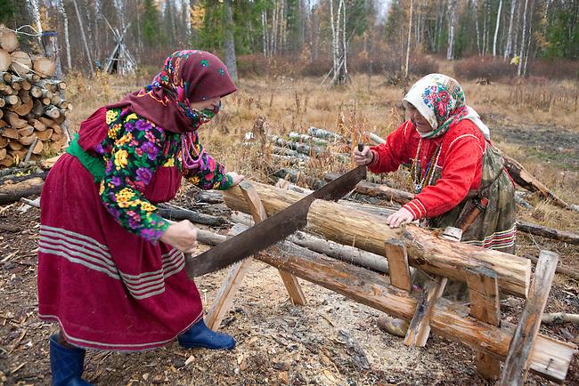 Vera & Irina Purgurchina, two Khanty women, sawing firewood outside their home on the bank of the Synya River. Yamal, Western Siberia, Russia