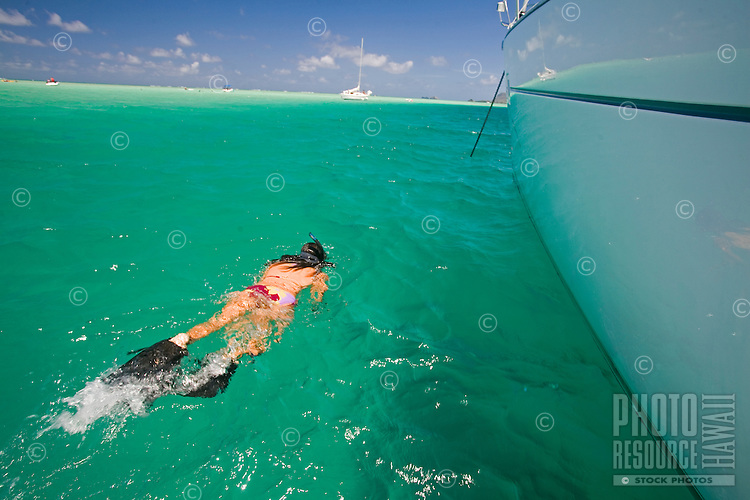 Young girl in bikini snorkeling next to a sailboat in Kaneohe Bay, Oahu, Hawaii