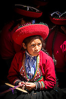 Local girl in traditional dress weaving at Chinchero Town Sunday Market, Cusco Region, Peru, South America