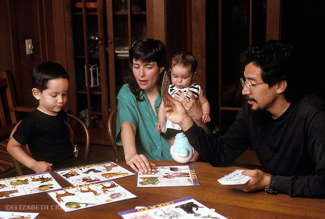 Berkeley CA Nuclear family playing animal lotto game together, Latino father, children three and a half, and six-months-old  MR