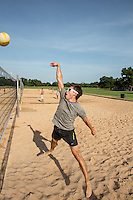 Man playing beach volleyball diving after the ball under a clear blue sky at Zilker Park sand volleyball courts