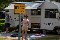 Switzerland. Canton Ticino. Tenero. Camping Campofelice. A motorhome belonging to a swiss german family has just arrived. Mother and father are busy organizing the camping place. Their daughter, still a baby, lies on her back on a cover laid on the grass. A campervan (or camper van), sometimes referred to as a camper, or a caravanette, is a self-propelled vehicle that provides both transport and sleeping accommodation. A motorhome (or motor coach is a type of self-propelled recreational vehicle (RV) which offers living accommodation combined with a vehicle engine. Motorhomes are part of the much larger associated group of mobile homes which includes caravans, also known as tourers, and static caravans. Campers are restricted to designated sites for which fees are payable. 20.07.2018 © 2018 Didier Ruef
