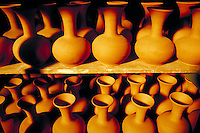 Rows of unglazed ceramic vases sit on shelves in a factory. Cyprus Mediterranean.