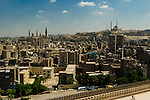 Cairo, Egypt -- Saladin's citadel (on right) and the Sultan Hassan Mosque and madrassa (left) frame the Cairo skyline when viewed from the minaret of the ibn Tulun mosque.  (The outer wall of the ibn Tulun mosque is also visible in the close foreground.) © Rick Collier / RickCollier.com