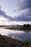 clouds reflect in still water of Oxbow Bend at dawn