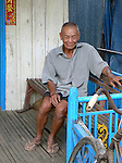 A man sits in front of his house in Kompong Chhnang, Cambodia
