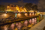 France, Paris.  <br /> If you don't have a tripod, hold onto the camera strap, then rest your camera on something solid like a guardrail. Then use the shutter timer for even less vibration.<br /> Visitors along the Seine River at night, Paris, France.