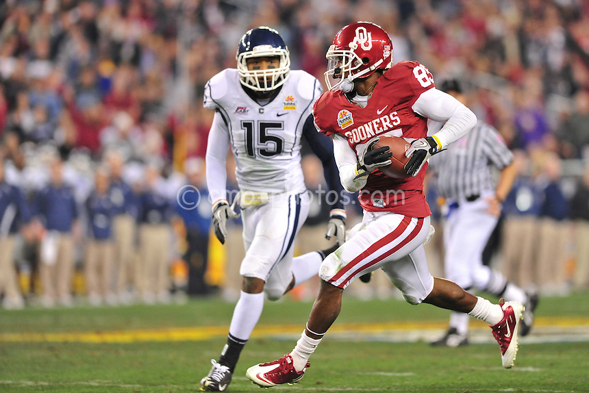 Jan 1, 2011; Glendale, AZ, USA; Connecticut Huskies safety Jerome Junior (15) tries to chase down Oklahoma Sooners wide receiver Ryan Broyles (85) during a punt return in the 3rd quarter of the 2011 Fiesta Bowl at University of Phoenix Stadium.  The Sooners won the game 48-20.