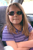 Girl age 7 chilling with arms folded wearing sunglasses.  St Paul  Minnesota USA
