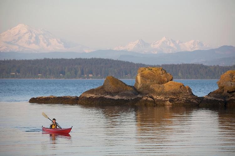 San Juan Islands, Sea kayaker, woman, Mount Baker, Clark Island Marine State Park, Salish Sea, Washington State, Pacific Northwest, U.S.A.,
