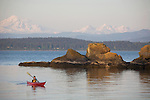 San Juan Islands, Sea kayaker, woman, Mount Baker, Clark Island Marine State Park, Salish Sea, Washington State, Pacific Northwest, U.S.A.,
