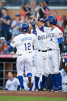 Alexi Casilla (12) of the Durham Bulls gets high fives from teammates Hak-Ju Lee (3) and Luke Maile (26) after hitting a 2-run home run against the Scranton/Wilkes-Barre RailRiders at Durham Bulls Athletic Park on May 15, 2015 in Durham, North Carolina.  The RailRiders defeated the Bulls 8-4 in 11 innings.  (Brian Westerholt/Four Seam Images)