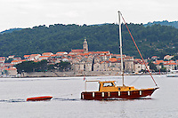 View across the sea on the town of Korcula on the island of the same name where Marco Polo was born. A small pleasure boat with a dinghy passing in front on the water. Korcula Island. Dalmatian Coast, Croatia, Europe.
