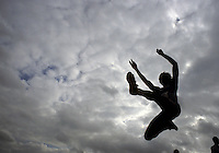 Female long jumper seen from below against stormy skies