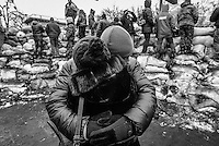 Behind the protection of trench sandbags, a woman hug his man who has been fighting for days