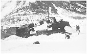 Engineer's-side view of D&amp;RGW #459 with large pilot snow plow, derailed in snow south of Silverton.  Three boys in snow beside train.<br /> D&amp;RGW  Silverton (s. of), CO  ca. 1937-1939