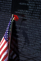 Vietnam Veterans Memorial Wall, Washington, DC, District of Columbia, A red carnation and the American Flag are placed by the names of loved ones who died in the Vietnam war on the Vietnam Veterans Memorial at West Potomac Park in Washington, D.C.