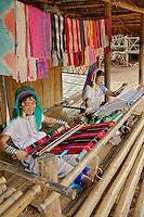 Adult Paduang Hilltribe women, or Long Neck Karen women, weaving in traditional methods, near Chiang Rai in norhtern Thailand.