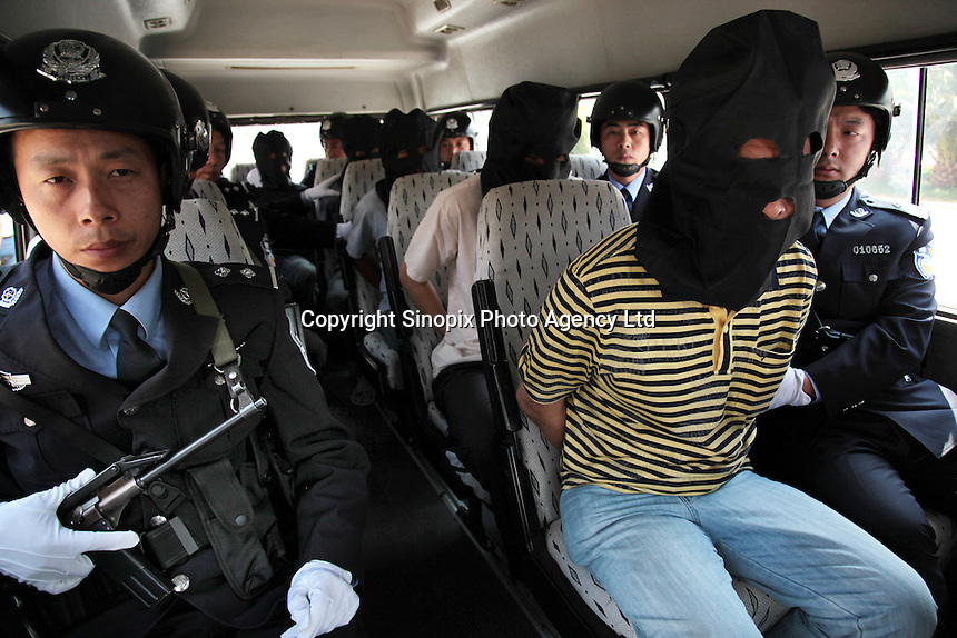 Police with a group of drug smugglers accused of smuggling 82 kilograms of amphetamines that in Jinghong, China. The drugs with a street value of at least 40 million RMB (about 6 million US$) were smuggled from Burma. Chinese-Burmese gangs smuggle drugs across the border and smuggle them out using drug mules. ...PHOTO BY SINOPIX