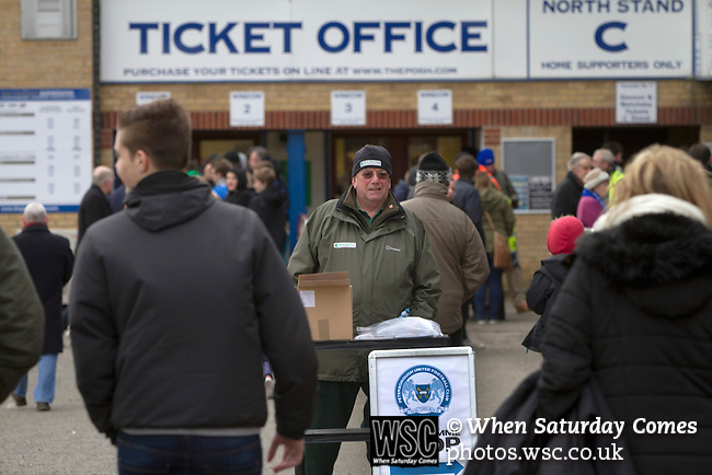 Peterborough United 1 Chesterfield 0, 21/03/2015. Abax Stadium, League One. A programme seller on duty outside the old main stand at the Abax Stadium, before Peterborough United play Chesterfield in a SkyBet League One fixture. The home team won the match by one goal to nil, watched by a crowd of 6,612. The result allowed Peterborough to leapfrog their opponents into the League One play-off positions with eight games remaining of the season. Photo by Colin McPherson.