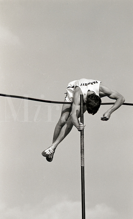 Male pole vaulter is clearing the bar.