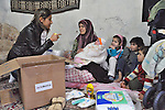 Rheam Abou-Ezze (left), a nutritionist for International Orthodox Christian Charities, explains the contents of a baby kit she is delivering to Khadoug Sawady, a Syrian refugee woman who just gave birth to a baby girl, Sajida Jallol, in the village of Lala in Lebanon's Bekaa Valley. The baby kit was provided by the IOCC and other members of the ACT Alliance which are assisting Syrian refugees in Lebanon in a variety of ways..
