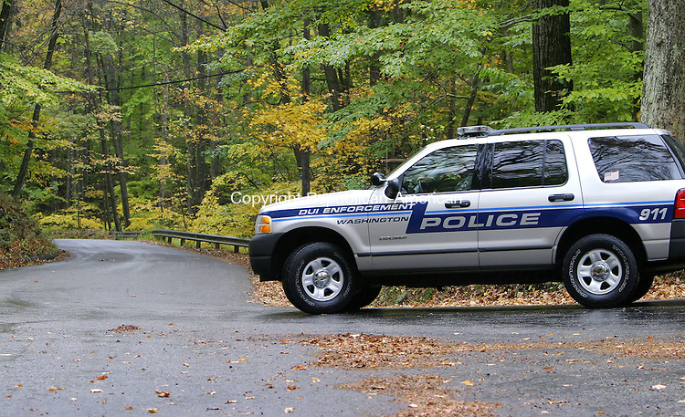 WASHINGTON, CT. 17 October 2006--101706SV02--A Washington police officer patrols the road where a jogger was attacked by a coyote on Lower Church Hill Road in Washington early Tuesday.<br /> Steven Valenti Republican-American
