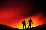 Silhouette of two men watching lava flow, Hawaii, USA.