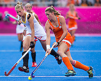 29 JUL 2012 - LONDON, GBR - Lidewij Welten (NED) of Netherlands (right) makes her way upfield pursued by Anne-Sophie van Regemortel (BEL) of Belgium (left) during their women's London 2012 Olympic Games Preliminary round hockey match at the Riverbank Arena in the Olympic Park in Stratford, London, Great Britain .(PHOTO (C) 2012 NIGEL FARROW)