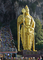 monumental golden statue of Shiva below stairs leading to Batu Cave sanctuary, time of Thaipusam ceremonies at Batu Caves, Kuala Lumpur, Malaysia, 2012. Thaipusam ceremonies, celebrated by tamile Hindu community in Malaysia, take place  in Sanctuary of Batu Caves at the border of Kuala Lumpur, each year around end of January or beginning of February, according to Hindu moon calendar. The event is paying hommage to Lord Murugan, a spirit or god created by Shiva to lead the army of gods against the army of evil demons, finally defeating the evil spirits. There are many ways to present offerings or sacrifices for this major religious event. Devotees mortify their bodies by carrying heavy kavaris with spears fixed in their skin or fruits, flowers and little post with holy milk fixed with hooks in their skin, ascending the stairways to the sanctuary in trance, `followed by assistant  taking care and musicians playing loud and fast rhythmic trance music.  Many families shave their head in a ritual before ascending the stairways, as part of rituals to obtain salvation for their ancestors.