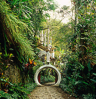 A circular concrete arch punctuates the stone pathway leading up the garden towards one of Edward James' installations