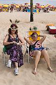 Two women watching carnival parade from Ipanema Beach, Rio de Janeiro