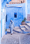 A woman draped in blue, walks in a blue city, Chefchauoen, Morocco