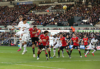 SWANSEA, WALES - FEBRUARY 21: Ki Sung Yueng of Swansea (2nd L) marked by Wayne Rooney of Manchester (3rd L) heads the ball over the crossbar during the Barclays Premier League match between Swansea City and Manchester United at Liberty Stadium on February 21, 2015 in Swansea, Wales.