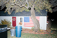 An American flag hangs on the side of a barn while Republican presidential candidate and former Florida governor Jeb Bush speaks to a crowd in the barn of Dr. and Mrs. James Betti in Rye, New Hampshire, for former Massachusetts senator Scott Brown's No B.S. BBQ series.