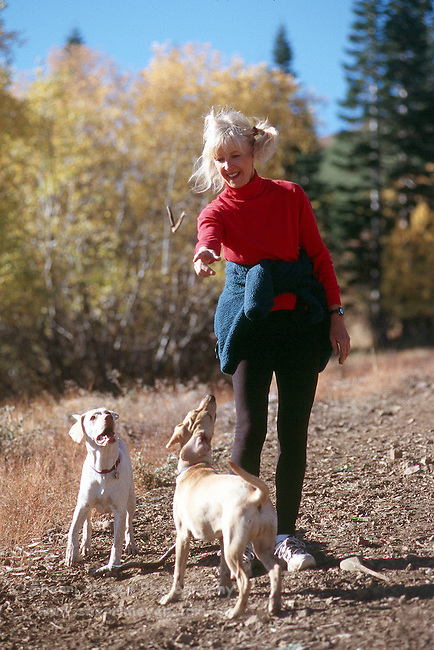 Woman stopping on the trail to play with her dogs